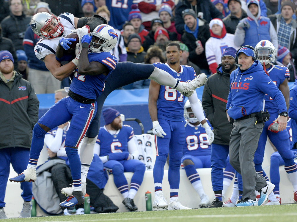 New England Patriots tight end Rob Gronkowski, left, makes a catch as Buffalo Bills cornerback Tre'Davious White (27) defends during the second half Sunday in Orchard Park, New York. Bills head coach Sean McDermott, right, looks on during the play.