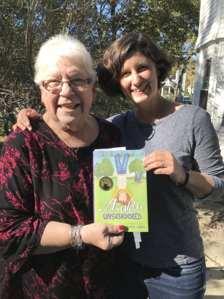 Oxford County Retired Educators Association member and chairperson of this year's Day of Caring Project Karen Ellis, left, receives a book from author Liza Kleinman, of Portland.