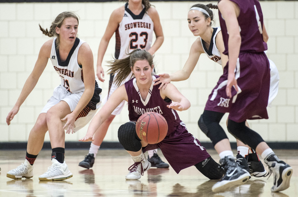Skowhegan forward Annie Cook, left, and teammate Emma Duffy, right, battle for a loose ball with Monmouth's Kaeti Butterfield during an exhibition game this preseason.