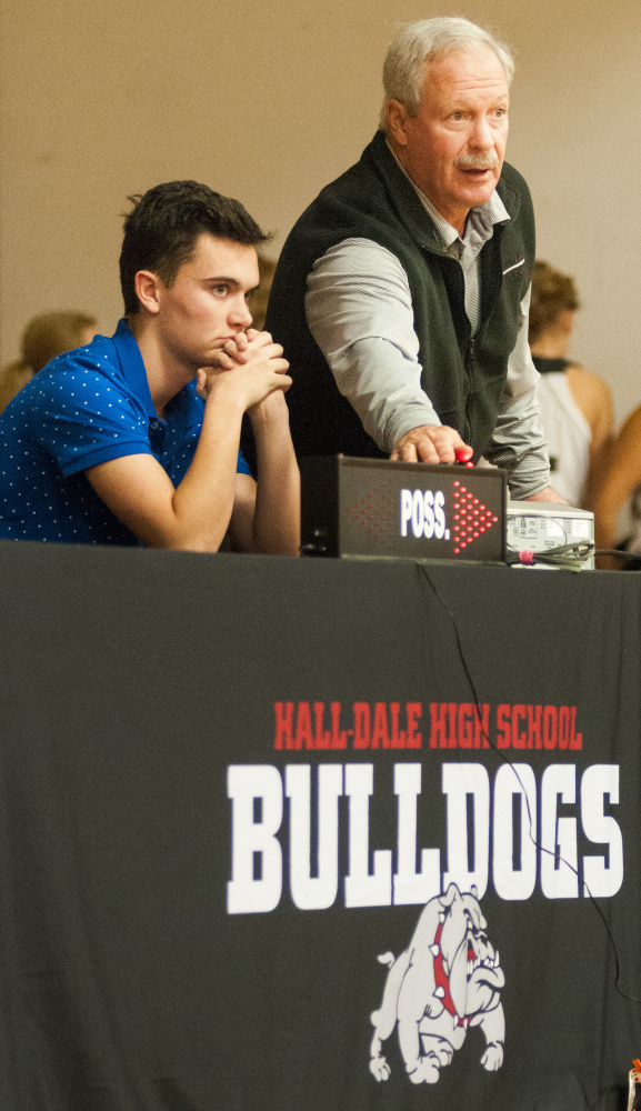 Athletic director Colin Roy, top, talks to scoreboard operator Logan Dupont about how to operate the alternating possession arrow sign at the scorers table on stage in the Penny Gym on Tuesday at Hall-Dale High School in Farmingdale. Roy was explaining that he should wait until the after an inbounds pass is actually caught before hitting the switch and flipping the arrow.