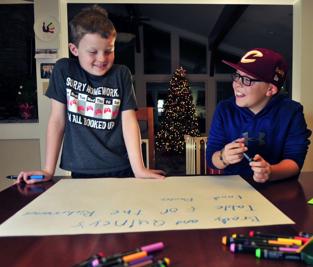 Quincy Emmons, left, and Brady Alexander work on a poster Thursday in Richmond before hosting a food drive at the Richmond tree lighting. Area residents responded, donating 1,280 food items for the cause.