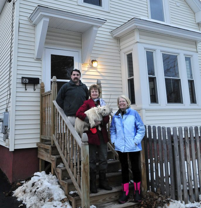 Waterville Community Land Trust members Scott McAdoo, Nancy Williams and Ann Beverage at a home the organization bought and is selling at 181 Water St. in Waterville on Monday.