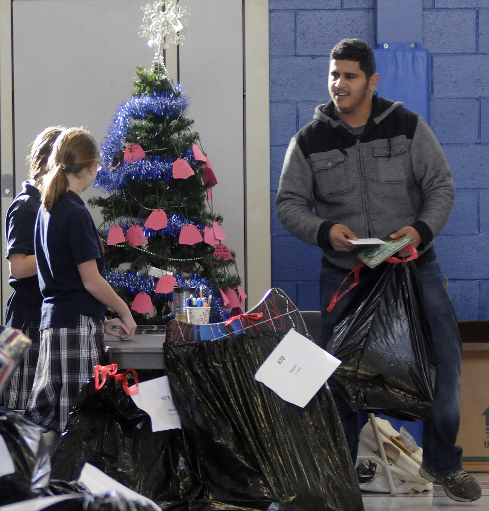 Malik Mousier collects gifts distributed by the Salvation Army on Dec. 20, 2016, at St. Michael School in Augusta.