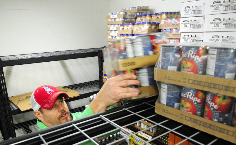 Warehouse manager Andy Waller stocks shelves Tuesday in the new Augusta Food Bank in Augusta.
