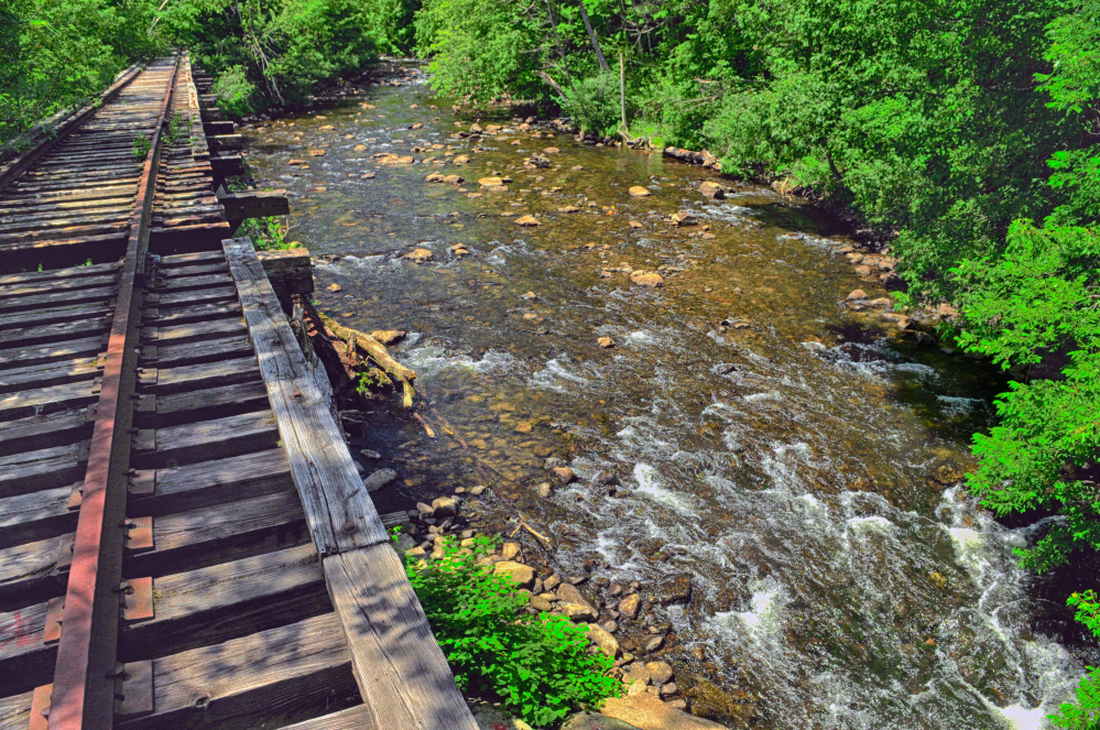 Cobbossee Stream in Gardiner is seen in June 2016 flowing under a railroad trestle. Officials are nearing completion of a plan for building a trail along the stream and are seeking input from downtown business owners on the impact of some design decisions.
