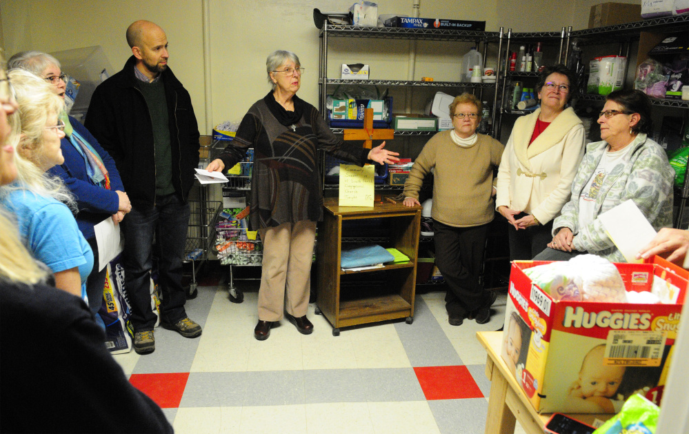 The Rev. Justin Frank, of Penney Memorial Baptist, left, and The Rev. Joan Smith, of South Parish Congregational Church, center, joined other local clergy in the The Everyday Basics Essentials Pantry at the end of a blessing ceremony on Thursday at the former St. Mark's Parish Hall on Pleasant Street in Augusta.