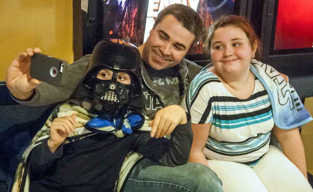 "Jake Sturtevant, center, takes a selfie with his children, Simon Sturtevant, 8, left, and Bella Sturtevant, 11, on Thursday before they go into the opening show of ""Star Wars: The Last Jedi"" at Regal Cinemas in Augusta."