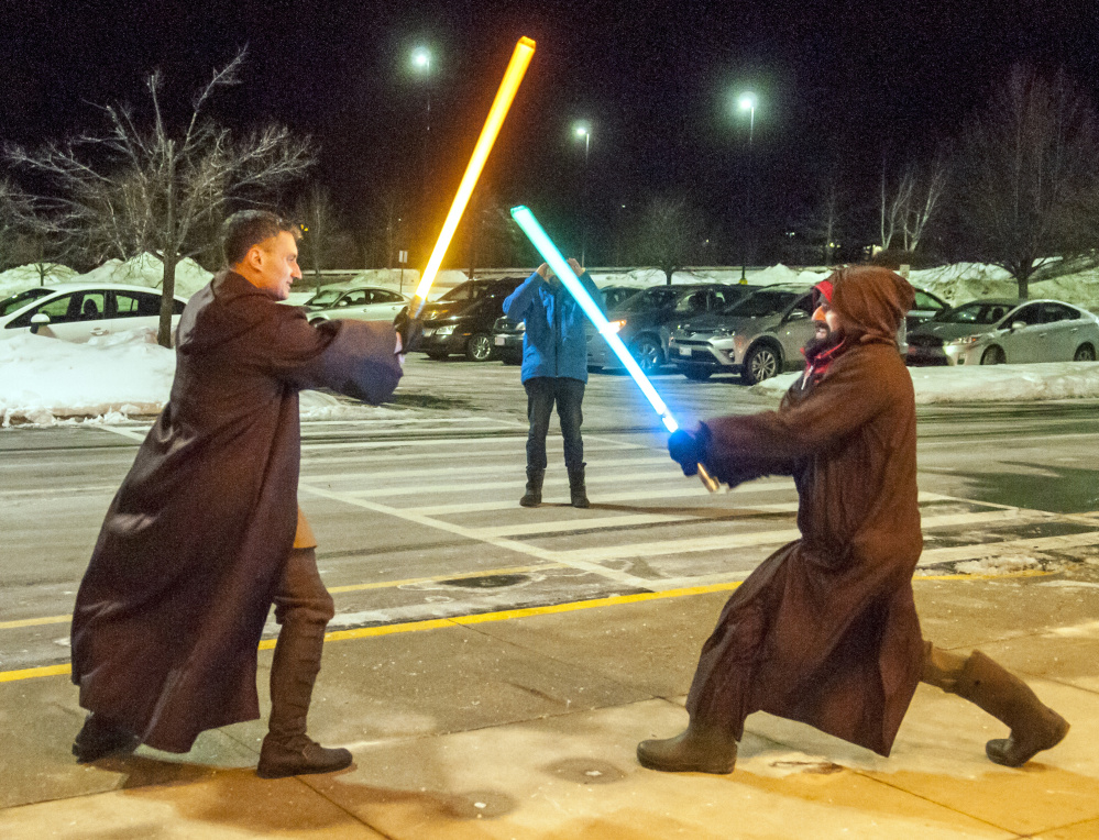 "Dressed in Jedi robes, Pete Spiegel, left, and Brian Juengest stage a lightsaber duel on the sidewalk before the opening show of ""Star Wars: The Last Jedi"" on Thursday at Regal Cinemas in Augusta."