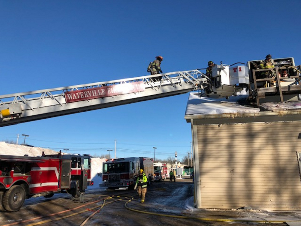 Firefighters work Friday from a Waterville Fire Department ladder truck on the heating and air conditioning unit on the roof of the Dairy Queen in the KMD Plaza mall off Kennedy Memorial Drive in Waterville.