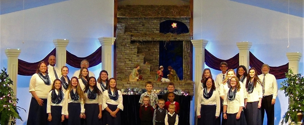 """Teen/adult choir members and junior choir members on the set of """"Christmas on the Air"""" to be presented at the New Hope Baptist Church, 268 Perham St. The adult choir group on the left, in front from left are Giulia Johnson, Georgia Cavenaugh, Haven Doyle and Erin Johnson; middle row, from left are JoAnne Doyle, Lydia Doyle, Kamrin Yates and Jessie Johnson; in back, from left are Kirk Doyle and Tom Charles. The childrens' choir in the center are, in front, from left, Elijah and Josiah Phillips; second row, from left are Micah Phillips and Autumn Decker; in back, from left are Evan Pinkham and Dalton Yates. The group on the right are, in front, from left, Sandi Rebert and Heather Wheeler; second row, from left are Madison Yates, Hannah Winters and Janna Winslow; in back, from left, are John and Valerie Trabucchi and Brian Rebert."""