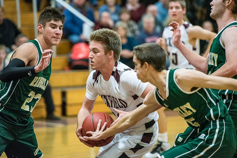Buckfield's Noah Wiley drives to the basket as Rangeley's Leonardo Perez and Ian Lillis defend during a Class D South game Friday night in Buckfield.