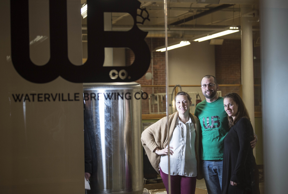 Waterville Brewing Company co-owners Amber Willett, left, Ryan Flaherty, center, and Candice Flaherty, pose for a portrait at their Hathaway Creative Center location on Thursday.
