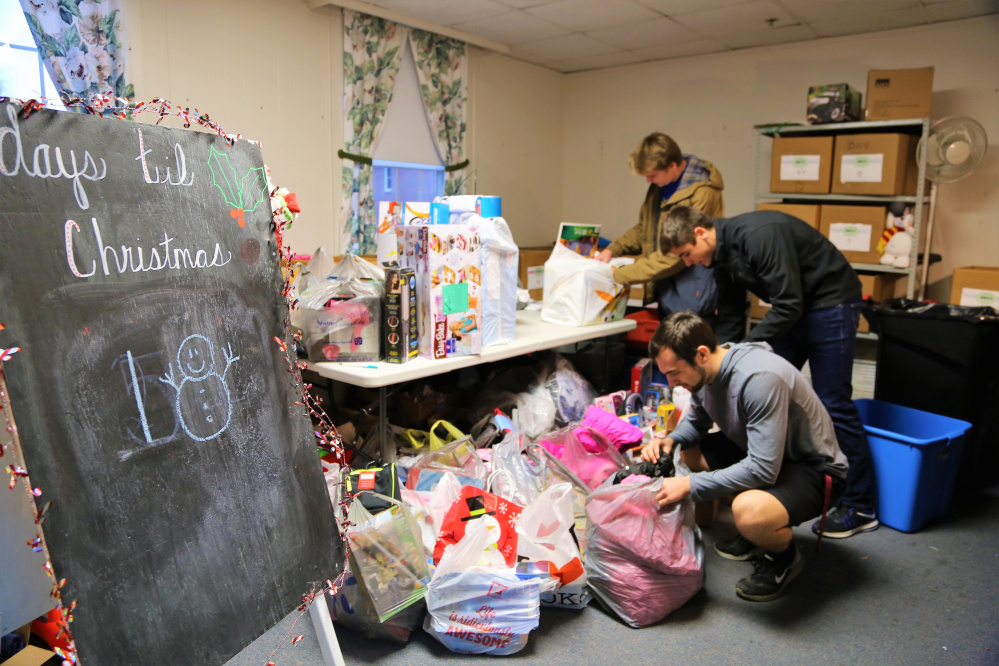 Messalonskee High School students, from front to back, Noah Tuttle, Chase Warren and Colby Charette help deliver a roomful of gifts that were donated to the ShineOnCass Foundation benefit Warming Up for Christmas. In addition to concert goers, the school's student council and athletic teams collected items to help fill the 1,700 boxes distributed to children through the Maine Children's Home for Little Wanderer's Christmas Program.