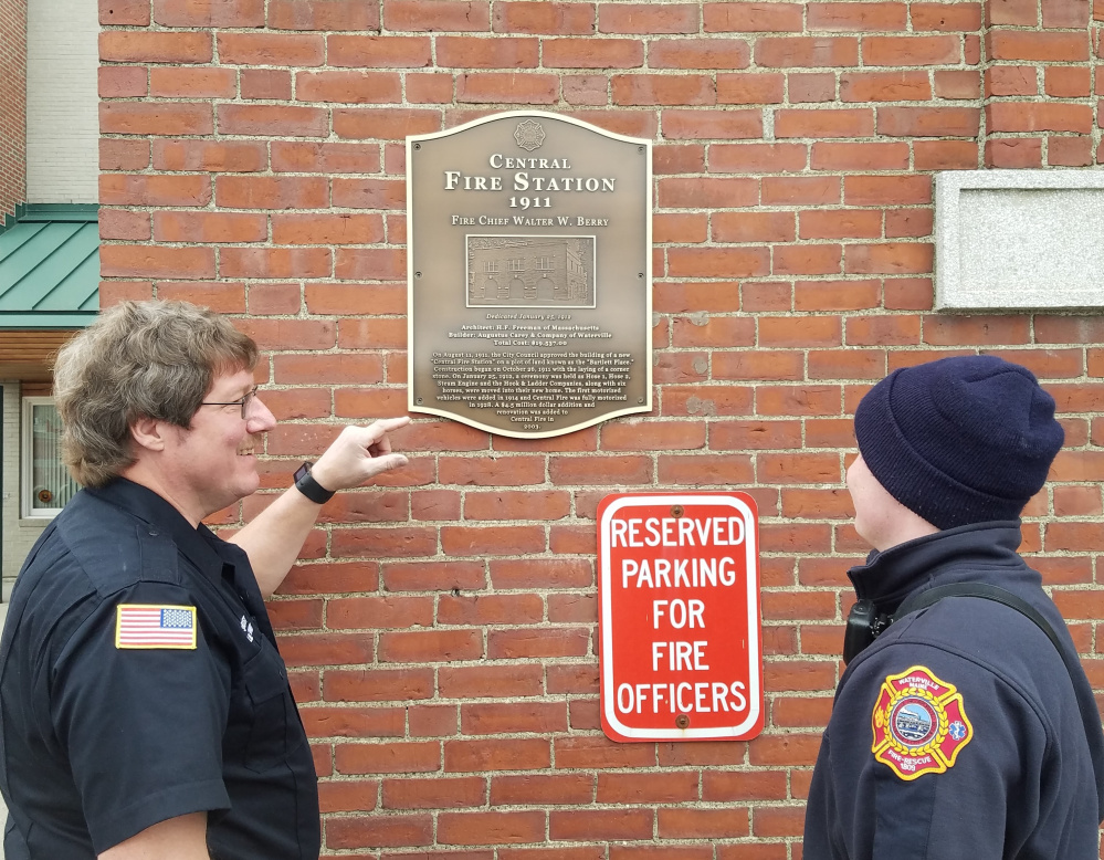 Lt. Scott A. Holst, left, and Firefighter Edward Moult look at the historical plaque commemorating the Old Central Fire Station recently was added to the building.