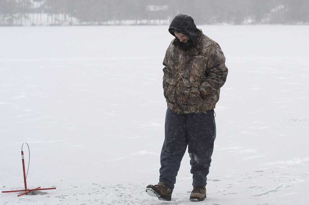 """Billy Gayton, of Leeds, waits Monday for a flag while ice fishing on Cochnewagon Lake in Monmouth. Gayton measured 5 inches of ice along the shore, where he placed traps, and 3 inches about 100 yards out. The shelf encouraged him to wait patiently in freezing temperature to catch a fish. """"I got to take care of that itch somehow,"""" he said."""