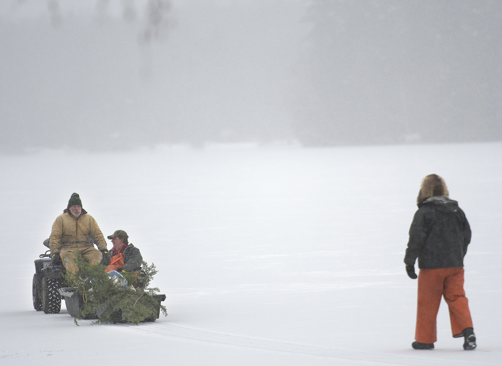 Men venture onto Cochnewagon Lake in Monmouth on Monday using an all-terrain vehicle and by foot. A recent cold snap has created a narrow shelf of ice on several shallow bodies of water across central Maine. The crew was erecting poles to mark snowmobile trails on the lake.
