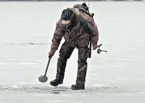Eric Crowly, of Monmouth, strains ice in a hole Monday on Cochnewagon Lake in Monmouth. The angler caught one brook trout beneath 5 inches of ice along the shoreline.