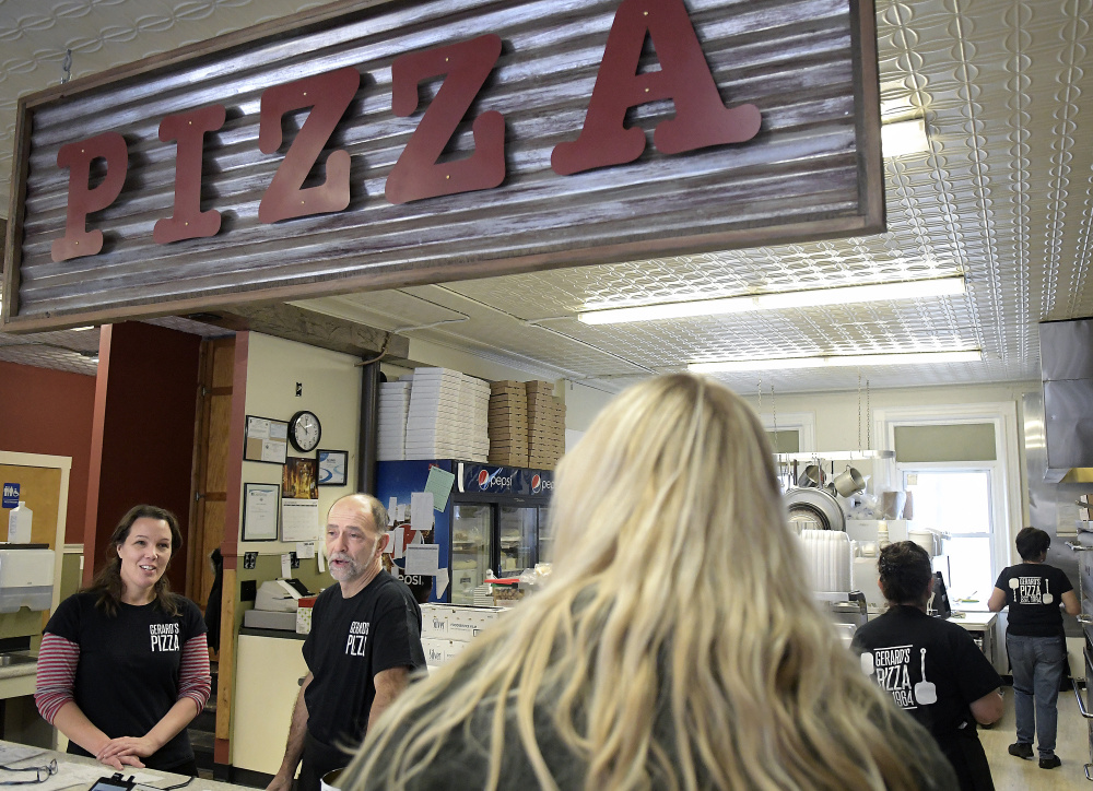 Gerard's Pizza owners Stacy and Claude Caron speak Tuesday with a customer at the Water Street business. The Gardiner institution reopened recently.