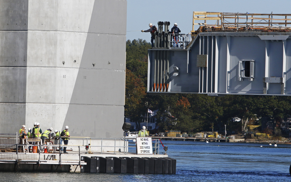 Dana Woods, center, a Cianbro supervisor, measures for clearance from the span back to the bridge tower as the span is positioned on Oct. 18 for connection to the Sarah Mildred Long bridge connecting Kittery to Portsmouth, New Hampshire. Cianbro has announced plans to hire about 300 workers for projects across the state, including improvements to a dry dock at the Portsmouth Naval Shipyard in Kittery.