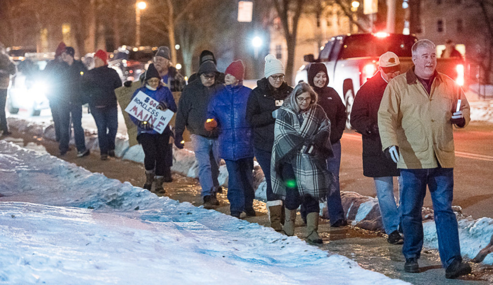 Chris Bicknell, far right, executive director of New Beginnings, leads a walking vigil in Lewiston to honor people who died while homeless during the past year and to raise awareness of homelessness.