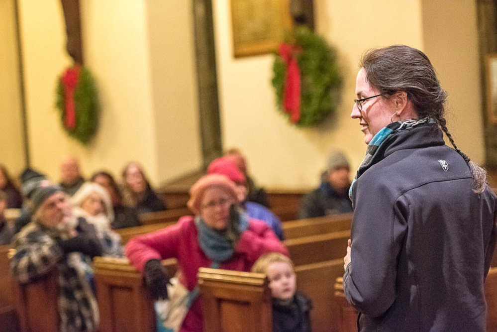 Erin Reed, executive director of Trinity Jubilee Center, addresses the crowd gathered for the Longest Night of Homelessness vigil at Trinity Episcopal Church in Lewiston on Thursday evening.