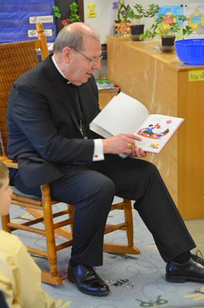 Bishop Robert P. Deeley reads a book to younger students at St. John Regional Catholic Church in Winslow.