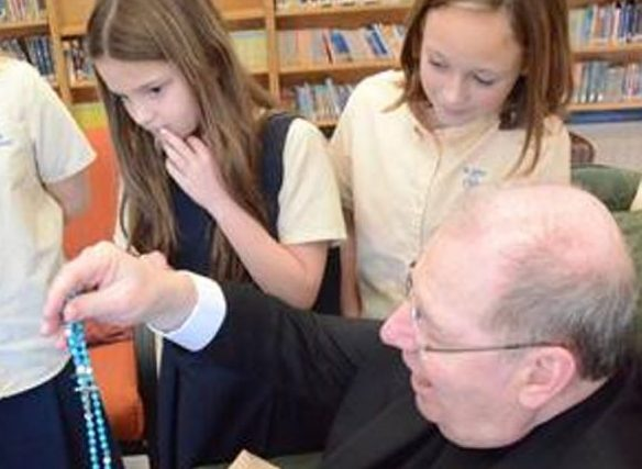 Bishop Robert P. Deeley opens a gift from the third and fourth graders of St. John Regional Catholic Church in Winslow.