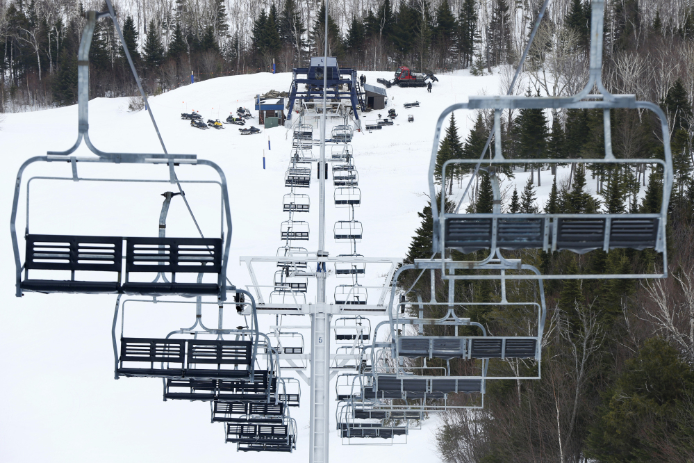 Workers repair the King Pine chairlift at Sugarloaf Mountain Ski Resort in Carrabassett Valley, on March 26, 2015. On Tuesday some skiers were stuck for five to 10 minutes because of a power outage that affected thousands in Franklin County.