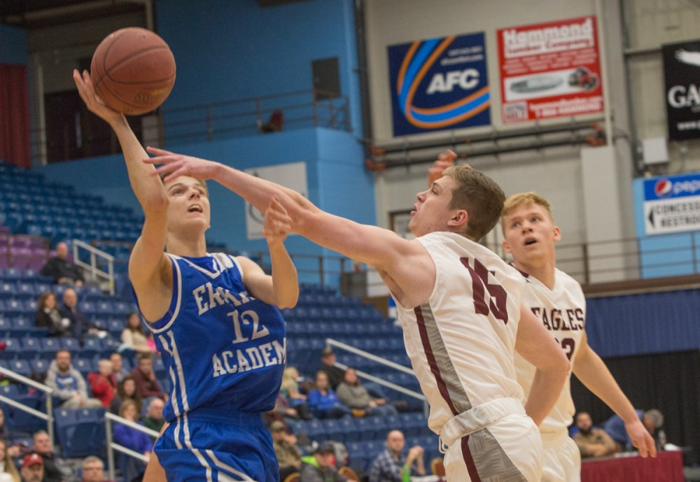 Erskine Academy's Austin Dunn (12) takes a shot while George Stevens Academy's Taylor Schildroth (15) defends at the Maine Gold Rush Invitational Tournament on Tuesday at the Augusta Civic Center.