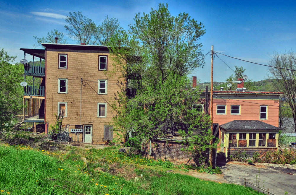 Dilapidated buildings at 11 State St., left, and 15 Morton Place, both in Augusta, are seen in May 2017 before the city demolished them. Officials now hope to sell the properties and return them to the tax rolls.