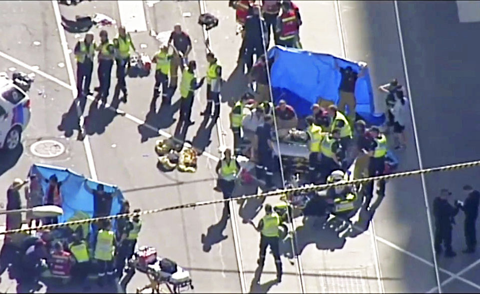 In this image from video, emergency medical workers offer aid to victims injured when an SUV drove into pedestrians on a sidewalk in central Melbourne.