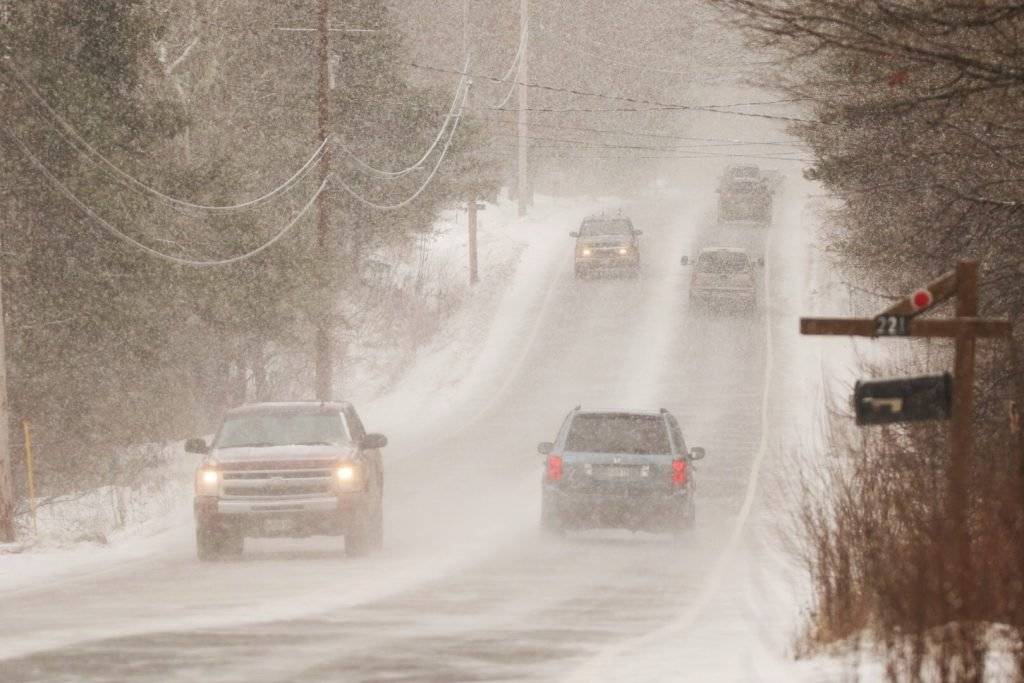 Motorists navigate heavy snowfall late Friday morning on Route 22 in Gorham.