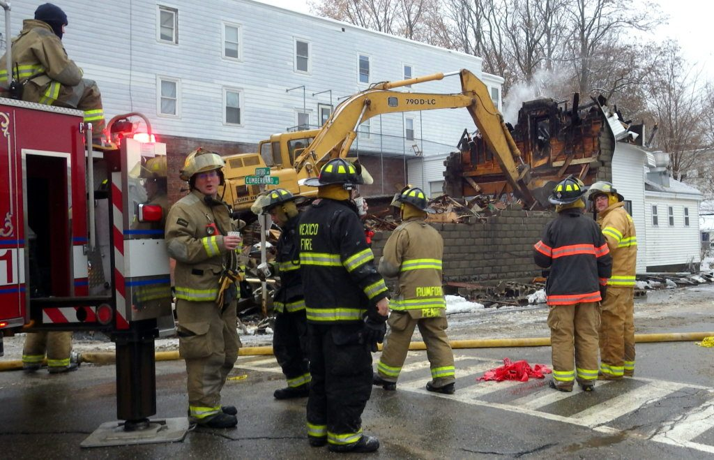 After battling an early morning fire Tuesday at the corner of Oxford Avenue and Cumberland Street in Rumford, firefighters watch an excavator tear down the burnt portion of the unoccupied building.