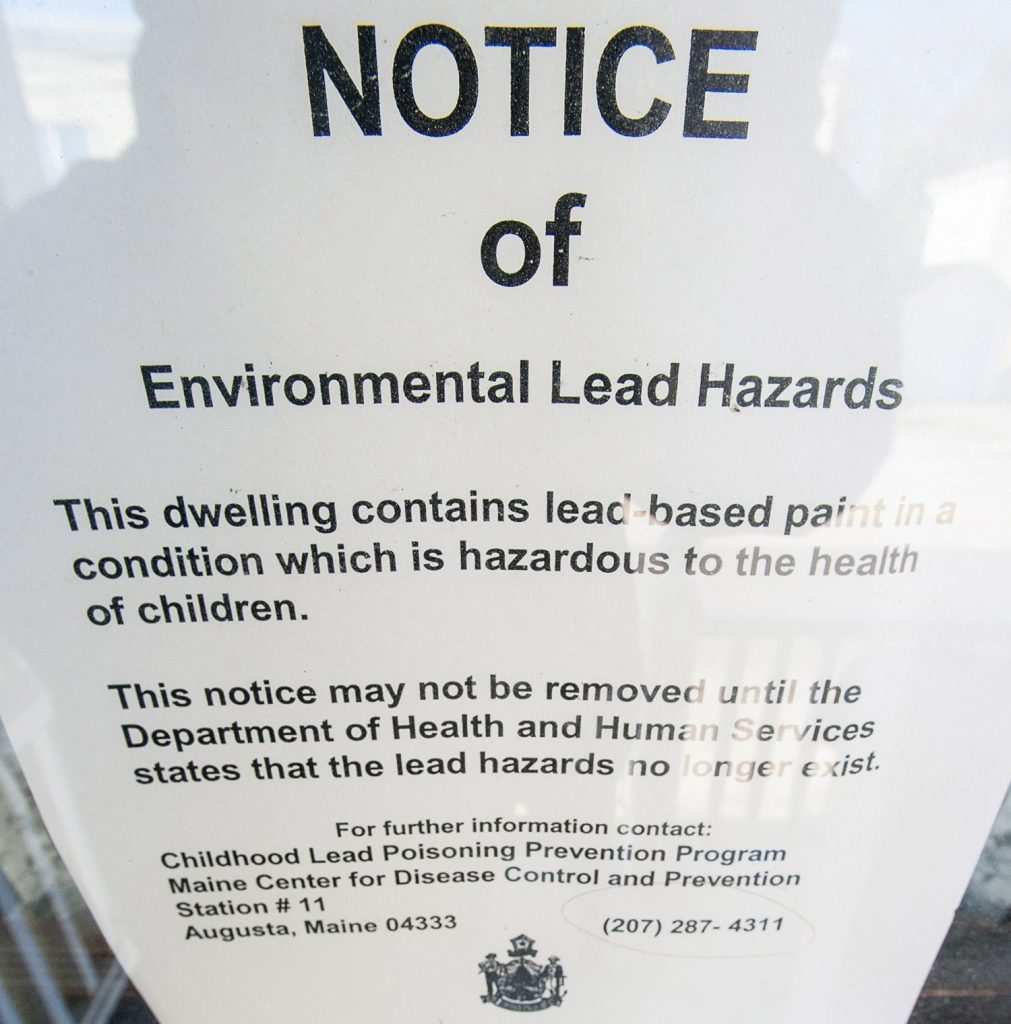 A lead paint notice on the storm door on the side porch entrance at 144 Walnut Street in Lewiston.