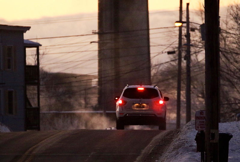 An early morning motorist drives across the Pine Street bridge, from Saco to Biddeford, as steam created by the negative 12-degree temperature rises from the Saco River in the background.