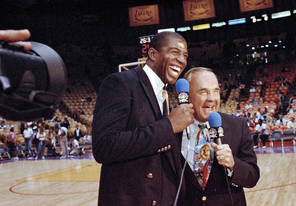 "Dick Enberg assists  Earvin ""Magic"" Johnson during Johnson's debut as a sports commentator at a Lakers-Bulls game on Feb. 2, 1992. The sportscaster who got his big break with UCLA basketball and went on to call Super Bowls, Olympics, Final Fours and Angels and Padres baseball games, is remembered for his kindness to newcomers to broadcasting – the ""definition of a gentleman."""