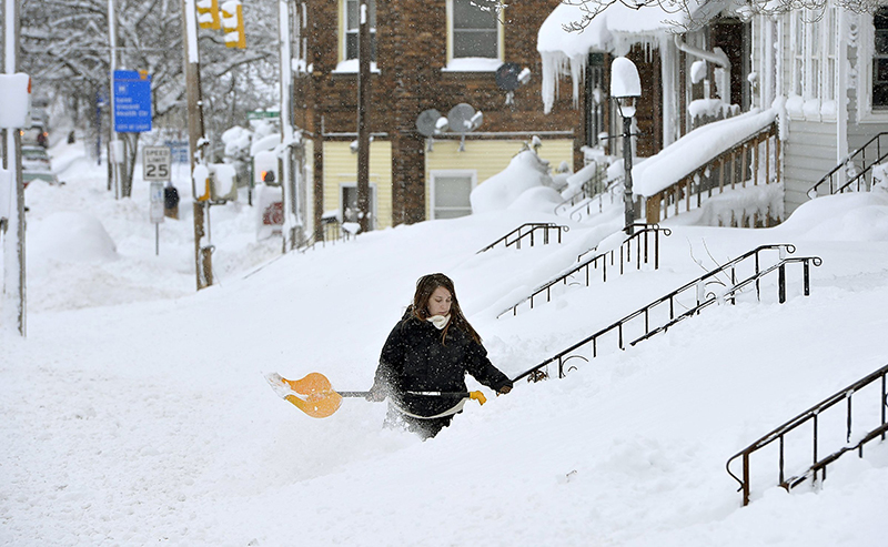 Rochelle Carlotti, 28, shovels steps near her home after a record snowfall on Tuesday,  in Erie, Pa.