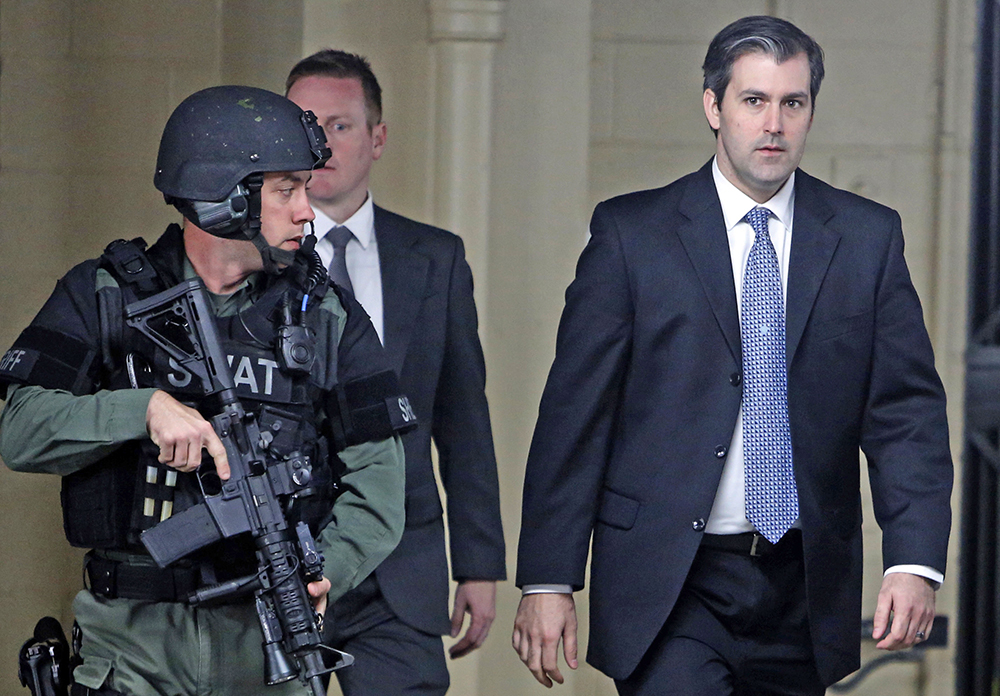 Former South Carolina officer Michael Slager walks from the Charleston County Courthouse under the protection of the Charleston County Sheriff's Department on Dec. 5, 2016.