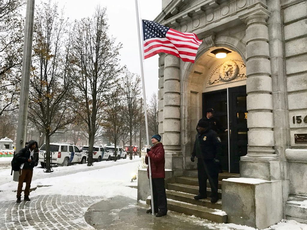 Rob Levin of Portland, who is a Quaker and an attorney, stands with a flag at half-staff in front of the federal courthouse in Portland on Tuesday to signify his disapproval of the Trump administration's plan to withdraw the U.S. from the Paris climate agreement. Levin was detained briefly after refusing to leave but was released without charges.