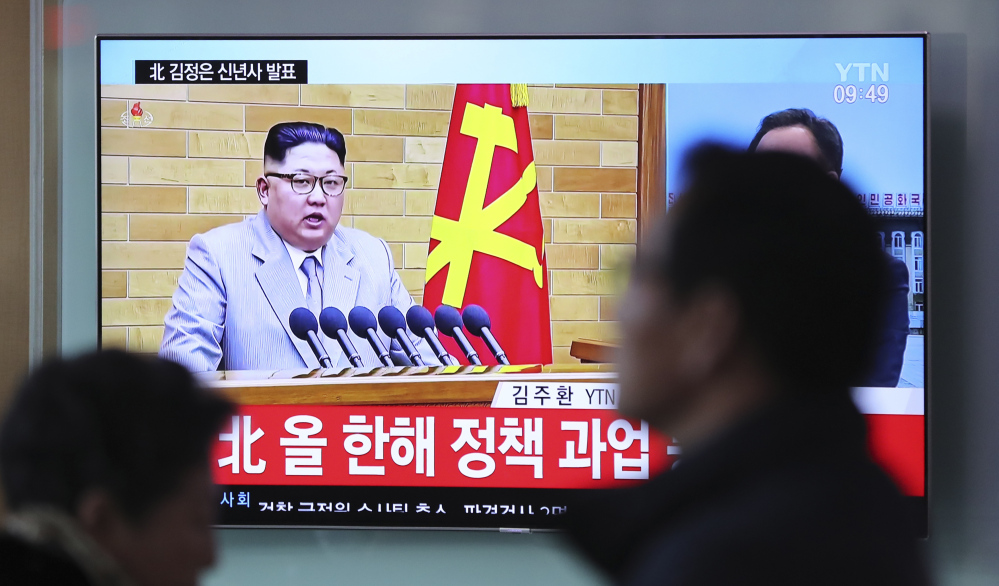 Visitors walk by a TV screen showing a news program reporting about North Korean leader Kim Jong Un's New Year's speech at the Seoul Railway Station in South Korea.