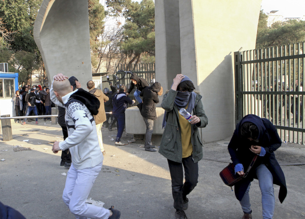 University students run away from stones thrown by police during an anti-government protest inside Tehran University, in Tehran, Iran. The photo was taken on Dec. 30, 2017, by an individual not employed by the Associated Press and obtained by the AP outside Iran.