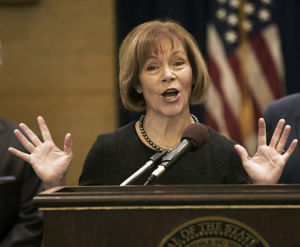 FILE - In this Wednesday, Dec. 13, 2017, file photo, Minnesota Lt. Gov. Tina Smith speaks as Gov. Mark Dayton listens during a news conference in St. Paul, Minn., as Smith was named to replace fellow Democrat Al Franken in the U.S. Senate. Franken announced his resignation a week earlier amid growing sexual misconduct allegations. Smith is vowing to