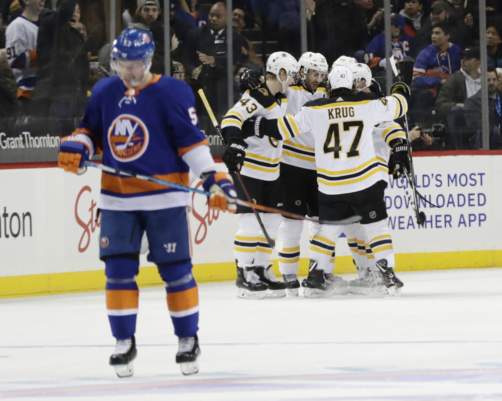 The Bruins' Patrice Bergeron celebrates with teammates Danton Heinen, 43, and Torey Krug, 47, after scoring a goal as the Islanders' Casey Cizikas, 53, skates away during the second period Tuesday in New York.
