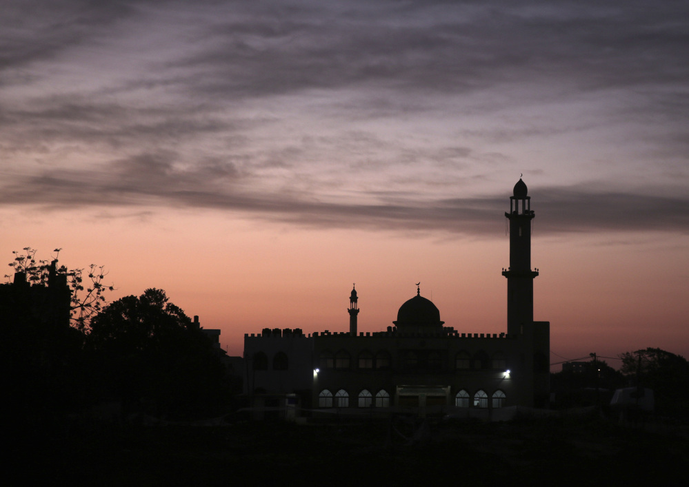 The sun rises over a mosque in Gaza City. In recent weeks, Gaza residents have been jolted awake in the dead of night to a raucous mixture of Quranic phrases, Islamic supplications and prayers delivered to their doorsteps.