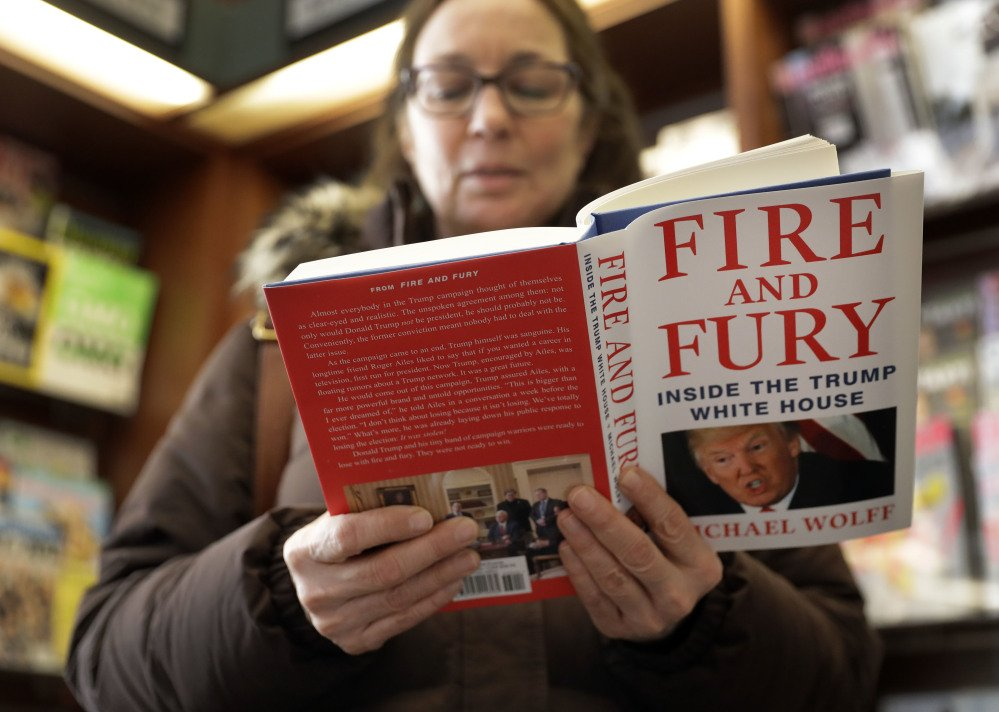 "Susan Mallin of Glenview, Ill., looks over a copy of ""Fire and Fury: Inside the Trump White House"" on Friday in Chicago."