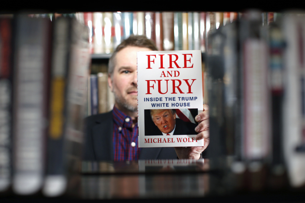 "Kevin Davis, director of the South Portland Public Library, with ""Fire and Fury,"" which President Trump has assailed. The library was listed online Friday as the only one in Maine with a copy."