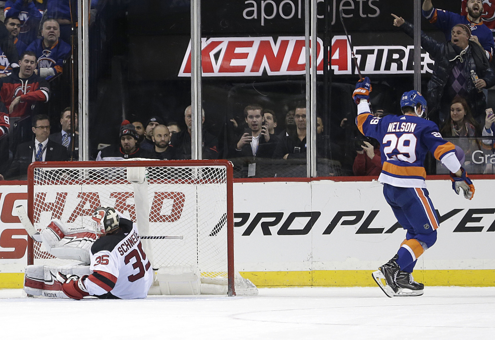 The Islanders' Brock Nelson, right, reacts after scoring the winning shootout goal against Devils goaltender Cory Schneider in New York's 5-4 victory at home Sunday.