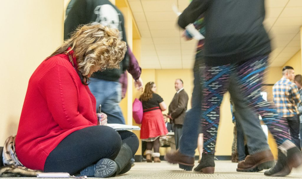 Sitting on the floor of a hallway outside the hearing room, Penny Snider, a medical marijuana caregiver from Pittston, writes out her testimony on Tuesday as she prepares to testify before the Marijuana Law Implementation Committee in the Cross State Office Building in Augusta.
