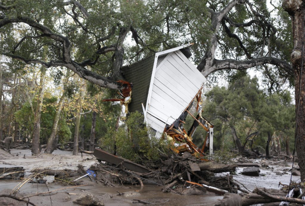 A structure is smashed against a tree along Hot Springs Road in Montecito, California, after getting hit by a flash flood and debris on Tuesday. Several homes were swept away before dawn Tuesday when mud and debris roared into neighborhoods in Montecito from hillsides stripped of vegetation during a recent wildfire.