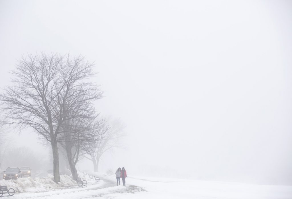 Kerri Smith and Allison Keely, right, both of Portland, tread carefully on a path along the Eastern Promenade, which is shrouded in fog from the melting snow Friday. Cold temperatures are expected to return this weekend.